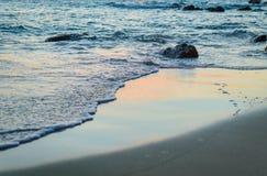 Wave of the sea on the sand beach. Seashore on sunset Stock Photo