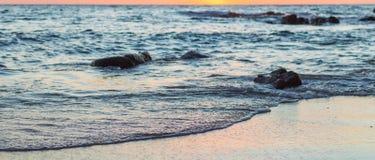 Wave of the sea on the sand beach. Seashore on sunset Royalty Free Stock Photos