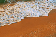 Wave of the sea on the sandy beach background with a lot of copyspace Royalty Free Stock Photo