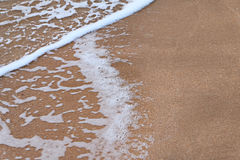 Wave of the sea on sandy beach a lot of space for text Royalty Free Stock Photos