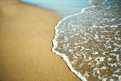 Wave of the sea on the sandy beach Stock Photos