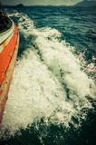 Wave of sea at the wooden boat side Stock Photos