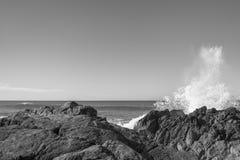 Wave si schianta sulle rocce fotografia stock