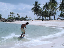 Wave skim surfing. Surfing at the water's edge at a seaside. The place is a tropical seaside resort area near the equator Stock Photography