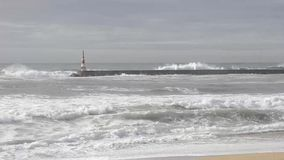 Wave splash on the Breakwater pier with lighthouse stock video footage