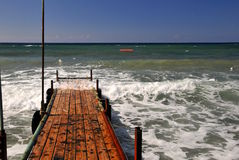 Wave splash at the pier. Rough waves ripple through a jetty on a wet and sunny day Royalty Free Stock Photography