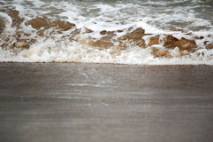 Wave splash on sand Royalty Free Stock Photography