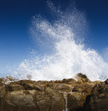 Wave splashing against rocks Royalty Free Stock Images