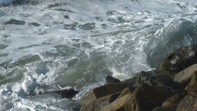 Wave Splashing Against the Rocks in Slow Motion. A wave crashes into the rocks.  Filmed in Slow Motion at 120fps 720p HD video stock video