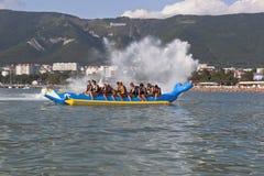 Wave splashing flying on of passengers inflatable banana. Beach activities in Gelendzhik Bay Stock Images