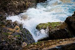 Wave splashing moss rock. Milky white wave. Close up shot royalty free stock image