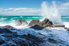 Wave splashing onto rocks Stock Photos