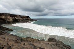 Wave splashing over a rock on the beach of Puertito de los Molinos on Fuerteventura. Royalty Free Stock Photography
