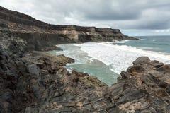 Wave splashing over a rock on the beach of Puertito de los Molinos on Fuerteventura. Royalty Free Stock Image