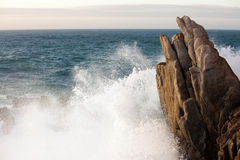 Wave splashing on rock Stock Photos