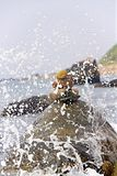 Wave Splashing on Rock. Wave spraying over large rock with pebbles on top Stock Image