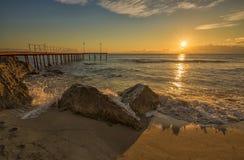 Wave splashing on the rocks. Sunrise over the sea with wave splashing on the rocks stock photos
