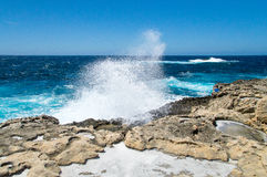 Wave splashing on the rocky coast with natural salt pans near missing Azure Window in Gozo Island, Malta. Stock Photos