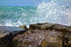 Wave spray againts rocks at sea ocean. Wave spray againts rocks at sea or ocean Royalty Free Stock Images