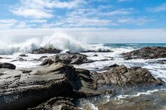 Wave with spray on californian coast. Wave with spray over some rocks in front of the californian coast stock images