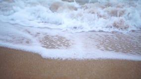 Wave spray splash over beach at blue sea. Soft wave on the sandy beach. Sea sunset stock video footage