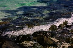 Wave on the stone coast. The water beats on the rocks on the shore of the island stock image
