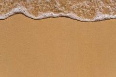 Wave sui precedenti della spiaggia di sabbia immagini stock libere da diritti