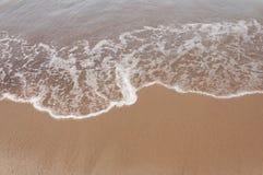 Wave sulla struttura del fondo della spiaggia Fotografia Stock