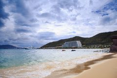 Wave Surf on Golden Beach Distant Hotel Sky Clouds. Wave surf on golden sand beach against resort city large hotel downhill vessel blue sky white clouds Royalty Free Stock Image