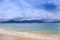 Wave Surf on Golden Beach Distant Resort City Sky Clouds. Wave surf on golden sand beach against distant resort city mountains boats big blue sky white clouds Stock Photography