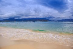 Wave Surf on Golden Beach Distant Resort City Sky Clouds. Wave surf on golden sand beach against distant resort city mountains boats blue sky white clouds Royalty Free Stock Photos