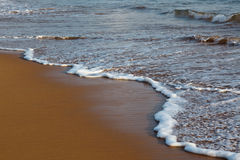Wave surging on sand Stock Photos
