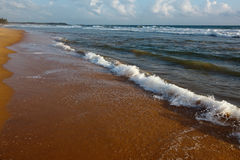 Wave surging on sand Royalty Free Stock Image