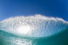 Wave Swimming Confrontation. Ocean wave wall surfer swimming view inside hollow crashing blue water face to face closeup Royalty Free Stock Image