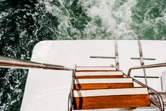Wave trace on sea water surface behind of fast moving power boat. Rear swim platform of boat. With wooden staircase and metal handrails. Top view stock photos