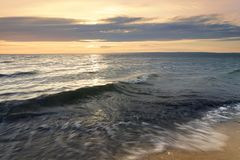 Wave in the troubled sea of dawn. The sun hid behind the clouds charm the dawn of a wild beach stock photo