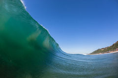 Wave Wall Upright Crashing. Upright standing ocean wave crashing on shallow reefs nearby beach coastline Stock Photo