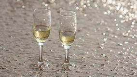 Wave washed away one of two glasses of champagne, standing on the sand on beach. Wave washed away one of two glasses of champagne, standing on the sand on the stock footage