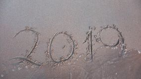 The wave washes the inscription 2019 off the sand. Outgoing Year Concept.  stock video