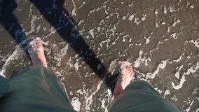 Wave washes over man`s legs in shorts on black sand. Shot with Sony a7s stock footage