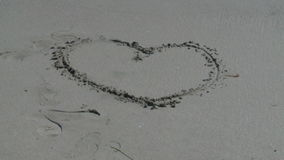 Wave washing away heart in sand. Video of wave washing away heart in sand stock footage
