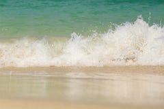 Wave washing up onto sand beach Stock Image