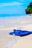 Wave washing up over sandals on a tropical beach. Stock Photo