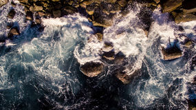 Wave of Water Hitting Brown Rocks Royalty Free Stock Images