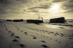 Wave water splash behind blockhouse on scenic beautiful sandy beach seascape with splashing waves Royalty Free Stock Photo