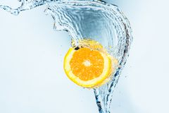 Wave of water splashing in a half orange. Against a light blue background royalty free stock images