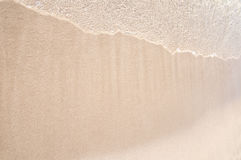 Wave on white sand Stock Images