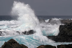 Wave and Wind. Wave breaking against the rocks with a strong wind Royalty Free Stock Photography