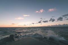 Wavebreaker in the sea - vintage effect. Wavebreaker in the sea with waves crushing over in sunset - vintage effect Stock Photos