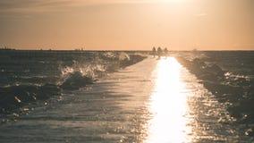 Wavebreaker in the sea - vintage effect. Wavebreaker in the sea with waves crushing over in sunset - vintage effect Royalty Free Stock Image
